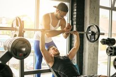 Personal trainer helping man in the gym. royalty free stock images