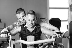 Personal trainer helping man with shoulder exercise. Personal trainer helping young men making seated rowing on a seated row machine - shoulder exercise - focus Royalty Free Stock Photos