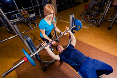 Personal trainer helping  men lift a barbell while working out in  gym. Personal trainer helping a men lift a barbell while working out in a gym Stock Photos