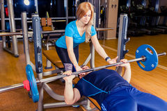 Personal trainer helping  men lift a barbell while working out in  gym. Personal trainer helping a men lift a barbell while working out in a gym Royalty Free Stock Photo