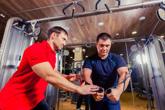 Personal trainer helping men working out in weights room at the gym Royalty Free Stock Photography