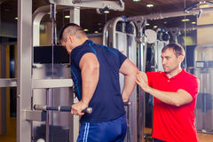 Personal trainer helping men working out in weights room at the gym Royalty Free Stock Photo