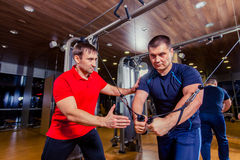 Personal trainer helping men working out in weights room at the gym Stock Photography
