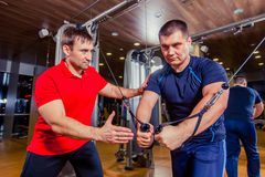Personal trainer helping men working out in weights room at the gym Royalty Free Stock Photos