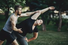 Personal trainer helping overweight woman at street workout. Fat. Personal trainer helping overweight women at street workout. Fat girl doing yoga with fitness Stock Photography