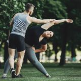 Personal trainer helping overweight woman at street workout. Personal trainer helping overweight women at street workout. Fat girl doing yoga with fitness Stock Image