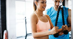 Personal trainer helping. Beautiful women in gym Royalty Free Stock Photography