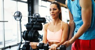 Personal trainer helping. Beautiful women in gym Royalty Free Stock Image