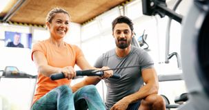 Personal trainer helping. Personal young trainer helping women in gym Stock Photo