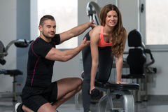 Personal Trainer Helping Woman On Back Exercise. Personal Trainer Showing Young Woman How To Train Back Exercise With Dumbbell In A Gym Royalty Free Stock Images
