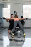 Personal Trainer Helping Woman On Back Exercise. Personal Trainer Showing Young Woman How To Train Back Exercise With Dumbbells In A Health And Fitness Concept Stock Image