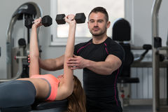 Personal Trainer Helping Woman On Chest Exercise. Personal Trainer Showing Young Woman How To Train Chest Exercise With Dumbbells In A Health And Fitness Concept Royalty Free Stock Image