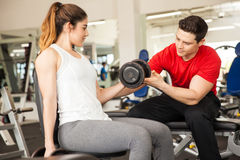 Personal trainer helping a woman at the gym. Attractive young personal trainer helping a young women with her posture while she lifts some weights at a gym Royalty Free Stock Photo