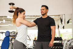 Personal trainer helping a woman at the gym. Hispanic personal trainer helping a young women with her posture while lifting some weights at the gym Stock Photos
