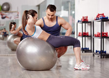 Personal trainer helping woman at gym. Personal trainer helping women doing abs crunches with gym ball Stock Photography
