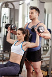 Personal trainer helping woman at gym Stock Images