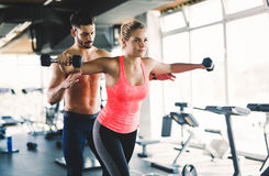 Personal trainer helping woman reach goals. Personal trainer helping women reach goals in gym Royalty Free Stock Photo
