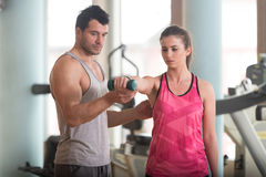 Personal Trainer Helping Woman On Shoulder Exercise. Personal Trainer Showing Young Woman How To Train Shoulder Exercise With Dumbbells In A Gym Stock Photo