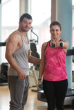 Personal Trainer Helping Woman On Shoulder Exercise. Personal Trainer Showing Young Woman How To Train Shoulder Exercise With Dumbbells In A Gym Stock Images