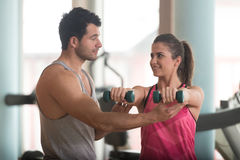 Personal Trainer Helping Woman On Shoulder Exercise. Personal Trainer Showing Young Woman How To Train Shoulder Exercise With Dumbbells In A Gym Stock Photography