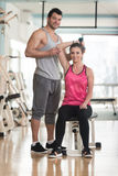 Personal Trainer Helping Woman On Triceps Exercise. Personal Trainer Showing Young Woman How To Train Triceps Exercise With Dumbbell In A Health And Fitness Royalty Free Stock Photography