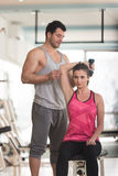 Personal Trainer Helping Woman On Triceps Exercise. Personal Trainer Showing Young Woman How To Train Triceps Exercise With Dumbbell In A Health And Fitness Royalty Free Stock Image