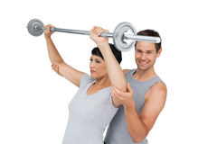 Personal trainer helping woman with weight lifting bar Royalty Free Stock Images