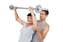 Personal trainer helping woman with weight lifting bar Stock Photography