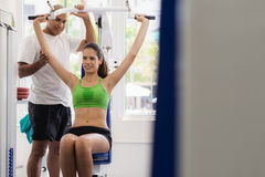 Personal trainer helping woman in wellness club. People and sports, men at work as personal trainer and helping young female athlete exercising in fitness gym Royalty Free Stock Image