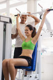 Personal trainer helping woman in wellness club Stock Photography