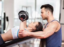 Personal trainer helping woman working with dumbbells Stock Photography