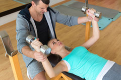 Personal trainer helping woman working with dumbbells Royalty Free Stock Photos
