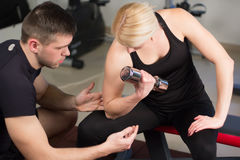 Personal trainer helping woman working with heavy dumbbells Royalty Free Stock Images