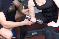 Personal trainer helping woman working with heavy dumbbells Stock Photos