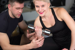 Personal trainer helping woman working with heavy dumbbells Royalty Free Stock Photos
