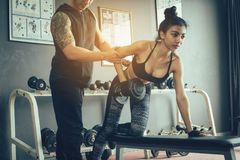 Personal trainer helping woman working lift heavy dumbbells. Personal trainer helping women working lift heavy dumbbells Royalty Free Stock Images