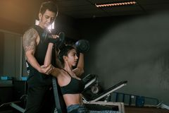 Personal trainer helping woman working lift heavy dumbbells two hand top a head royalty free stock photography