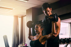 Personal trainer helping woman working lift heavy dumbbells two Stock Photos