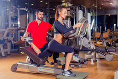 Personal trainer helping woman working with lunges, leg coaching Stock Photo