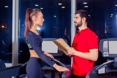 Personal trainer helping woman working with treadmill Stock Photo