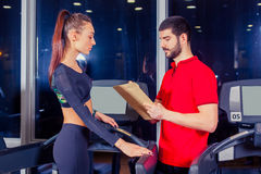 Personal trainer helping woman working with treadmill. Personal trainer helping women working with treadmill Stock Image