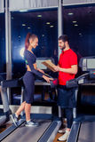 Personal trainer helping woman working with treadmill. Personal trainer helping women working with treadmill Royalty Free Stock Images