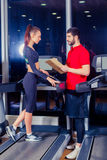Personal trainer helping woman working with treadmill Stock Photography