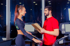 Personal trainer helping woman working with treadmill Royalty Free Stock Photo