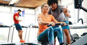 Personal trainer helping. Women in gym Stock Photography
