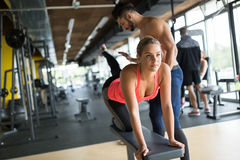 Personal trainer helping. Women in gym Stock Image