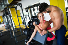 Personal trainer helping. Women in gym Royalty Free Stock Image