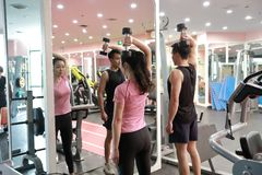 Asian chinese woman in gym lifting weights. Personal trainer helping women at gym,Woman in gym try with dumbbells Royalty Free Stock Photography