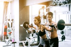 Personal trainer helping women and handle heavy barbells two han Royalty Free Stock Images