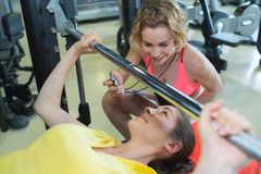 Personal trainer helping woman lift barbell royalty free stock photo